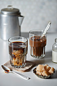 Iced coffee in a glass with cream and brown sugar cubes