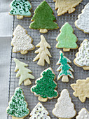 Christmas tree cookies with various decorations on a cooling rack