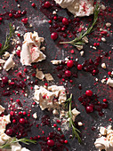 Crumbled meringue surrounded by squashed berries and rosemary sprigs