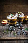 Vegan dessert made from chocolate cake, peach purée, whipped soya cream and coffee syrup in glasses