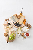 A cheese platter with dried fruit, grapes, pears, nuts and wholemeal bread