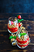Glasses of granola and strawberries layered parfait with mint for healthy breakfast
