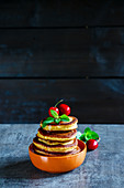 Homemade american pancakes topped with berries, honey and mint leaves