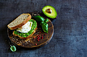Healthy avocado and poached egg sandwich with sesame seeds