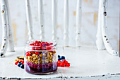 Tasty granola and fresh summer berry layered parfait in jar for breakfast