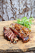 Grilled porterhouse steak with onions and rocket