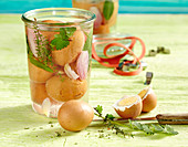 Herb pickled eggs in a jar with bay leaves, onions, garlic, thyme and burnet saxifrage