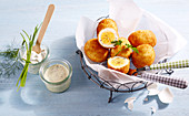 Breaded eggs in parchment paper in a metal basket next to a mustard dip and remoulade