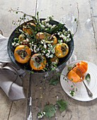 Persimmons with pernettya berries, heather and maidenhair arranged in a bowl
