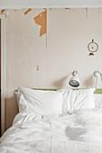 Weiße Bettwäsche auf Doppelbett, darüber Leselampe und Traumfänger an Wand mit abgeblätterter Tapete