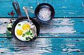 Healthy breakfast with fried eggs and green organic broccoli in old cast iron pan