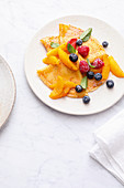 Crepes with oranges and fresh berries