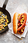 A hot dog with chili beans and potato cubes