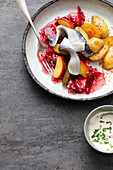 Pickled herring fillets with potatoes and beetroot in an elderflower marinade