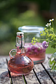 Homemade chive-flower vinegar in decorative carafe