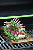 Raw rack of lamb with fresh herbs being prepared for grilling