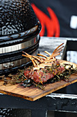 Grilled rack of lamb with herbs next to a kettle barbecue