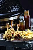 Gegrillte Hähnchenunterkeulen mit Crunch neben Grillgerät