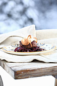 A beef fillet topped with gingerbread, on a bed of port infused shallots