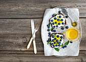 Healthy breakfast set with ricotta, fresh blueberries and honey sandwiches on whole grain bread