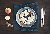 Pancakes with chocolate, yogurt, bananas and blueberries