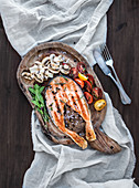Grilled salmon steak with fresh herbs, roasted mushrooms, cherry-tomatoes and spices