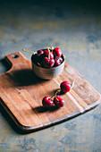 Frische Kirschen in Schälchen und auf Holzbrett