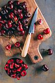 Frische Kirschen auf Holzschneidebrett mit Messer entsteinen