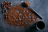 Coffee beans and ground coffee on dark background with the word Coffee written on it
