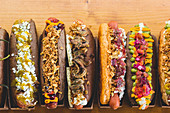 Row of assorted hot dogs with different delicious toppings and fillings