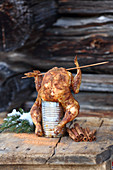 Grilled can chicken on a wooden table outdoors