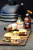 Three grilled burgers with sauces on a wooden board