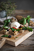 Crostini with mozzarella, olives, mussels, tomatoes, and basil leaves on a wooden board