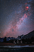Milky Way and nebulae over mountain valley in Tibet