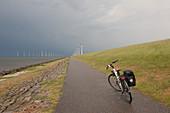 Bicycle on dike near wind turbines
