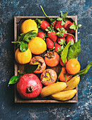Healthy fresh fruit variety: Oranges, lemons with leaves, pomegranate, bananas, strawberries and persimmon in wooden box