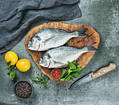 Fresh uncooked sea bream or dorado fish with lemon, herbs and spices in bowls