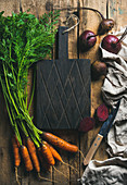 Fresh garden carrots and beetroots on rustic wooden background with dark cutting board