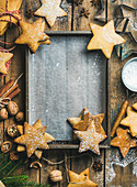 Gingerbread cookies, sugar powder, nuts, spices, baking molds, fir-tree branch on wooden background