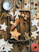 Gingerbread star shaped cookies, wooden angels, decorative stars, nuts and spices in wooden tray