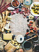 Wine and snack set with various wines in glasses, meat variety, bread, green olives, figs and berries on wax paper