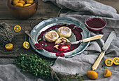 Russian cheese cakes on a vintage metal plate with lingonberry jam, fresh kumquats and thyme