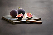 Fresh figs on a wooden board with a fruit knife