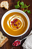 Cream of pumpkin soup with pomegranate seeds in a white bowl