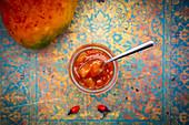 Mango chutney in a jar with a spoon