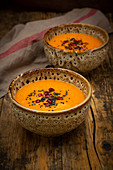 Oriental carrot, ginger and coconut soup with black sesame seeds and pomegranate seeds