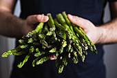 A person holding fresh green asparagus spears