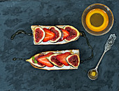 Fig and strawberry goat cheese sandwiches with honey on a dark stone surface