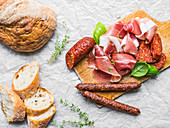 Meat appetizers selection, a loaf of rustic village bread and baguette slices on a white paper background