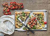 Rustikale Pizza mit Pilzen, Rucola und frischen Tomaten